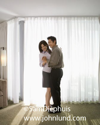 Asian couple dancing together in thier motel room.  They are in a waltz or slow-dance embrace. Romantic Asian pic.