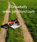 A young adventureous couple are sitting in the grass in the middle of a dirt road studying a map they have spread out on the ground in front of them. Road trip pics.