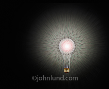 A light bulb against a background halo of hundred dollar bills in a stock photo about ideas, creativity and money.