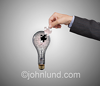 Creativity, innovation and ideas are expressed in this stock photo showing a businessman's hand about to add the final puzzle piece to a lightbulb image.