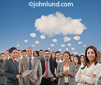 A crowd of people stand under a cloud sharing a thought bubble in a stock photo image about teamwork, crowd sourcing, cloud computing and connection.