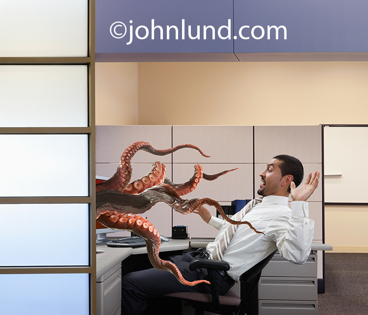 Sea monster tentacles reach out of a computer monitor attempting to snare a businessman seated at his computer.