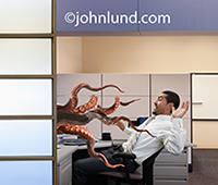 A businessman recoils in his cubicle as tentacles stretch out from his computer and attempt to grab him in a photo about cyber attackes.
