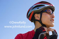 Close up photo of a man's head and face as he tightens his chin strap on his biking helmet. The man is wearing sunglasses and both of his hands are fidding with his chinstrap.  Blue sky background.  Fotos of athletes in action.