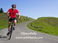 Stock photo of a man riding a bicycle on a gravel country road in rolling hills covered with thick green grass.  The sky is clear and blue on a bright sunny day. Perfect day for a bike ride in the country.