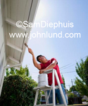 Picture of a man painting the trim on a house with a paint brush while standing on a step ladder.  He is painting under the eves. The sky is blue and he is wearing a red shirt. House painting pics.