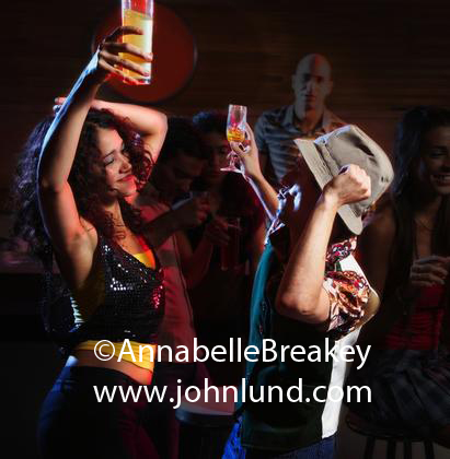 Couple doing some wild dancing, holding their drinks over their heads. Sexy dancing while out clubbing for the evening.  Dancing wearing a fedora. Dancing photo.