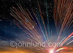 Streaks of colored lights representing an explosion and transmission of data streak out from a bright center through a dawn sky in a stock photo about future communications technology.
