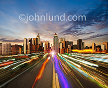 Streaming data on the information highway is seen in this stock photo of vividly colored light trails speeding down a highway to and from a distant metropolis.