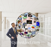 A smiling business man is surrounded by a globe of information in a demonstration of potential future communications search and database management technology.