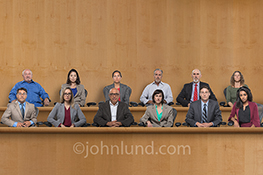 A jury of six men and six women sits impassively, almost ominously, with deadpan expressions in a stock photo about judgement, verdicts, and even the legal system.
