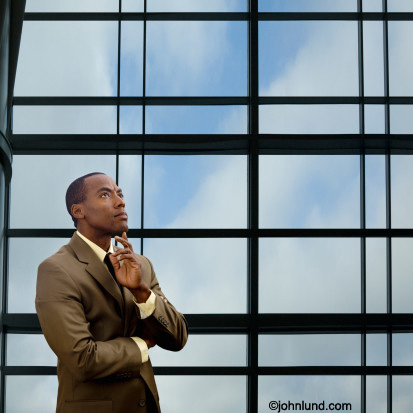 An African American business executive stands alone in a corporate enviroment and contemplates a decision he must make. The man is standing in front of a vast office window,looking up, and rubbing his chin.