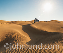 A four wheel drive vehicle, loaded with provisions, races across desert sand dunes in an image about exploration, discovery, adventure and getting away from it all.