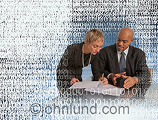 Two business people sign documents in a meeting surrounded by binary numbers in a stock photo about business, agreements and business success in the Internet age.