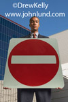 Picture of a black man holding up a do not enter traffic sign in front of him. Low angle shot. Camera looking up at man holding sign. Big red circle with white bar in the center.
