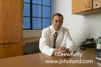 Doctor portrait. Picture for advertising of an ethnic doctor in a white lab coat sitting in his doctor's office with his hands clasped in front  of him. He is looking at the camera and has very short hair.