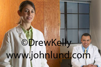 Photo of two doctors in their office, a woman doctor is standing on the left, and a man doctor is sitting on the right. Both are wearing white lab coats and are smiling at the camera. Pictures of doctors for advertising.