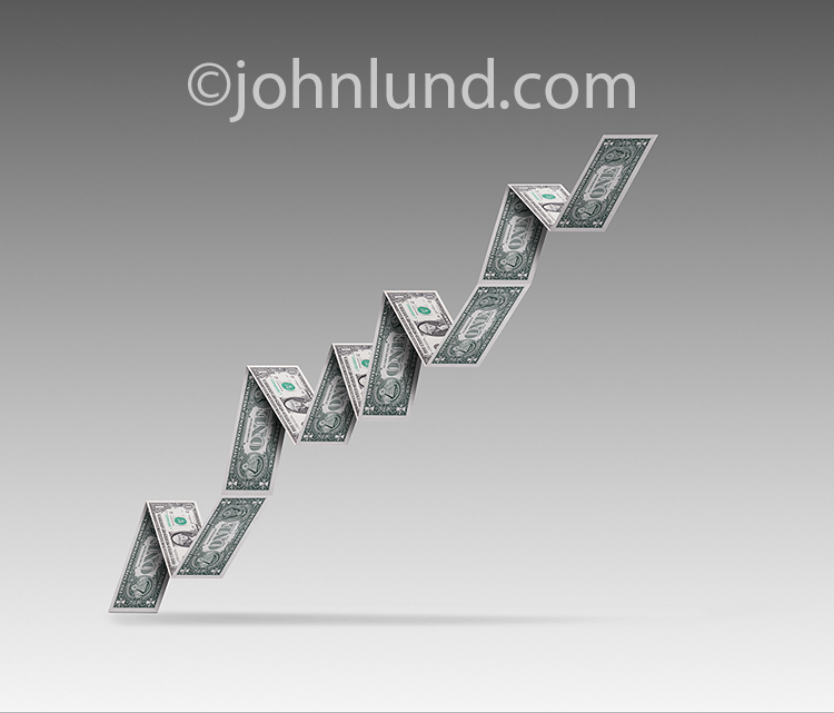 A business growth chart is composed of dollar bills ascending against a gradated gray background in a stock photo about business growth, success, finance and the economy.