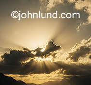 Dramatic god rays stream out from behind clouds over a mountain range in this stock photo about spirituality and the wonder and beauty of nature.