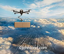 Pictures of Drones Delivering Packages Stock Photo. A drone at high altitude is seen carrying a package over a metropolis below.