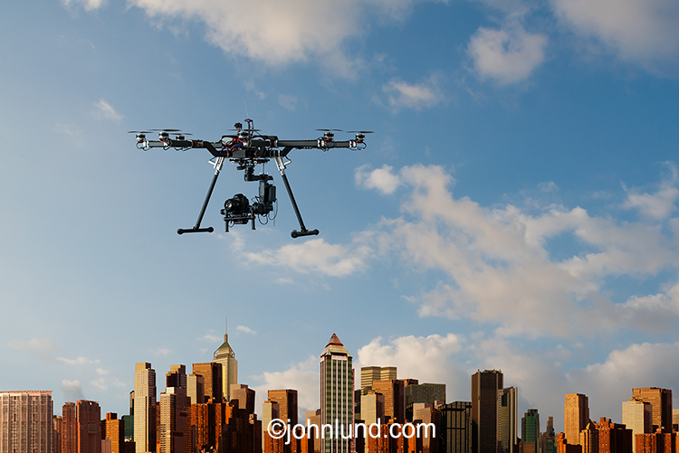 A camera equipped drone hovers over a large city in a stock photo about surveillance, privacy and other drone-related issues.
