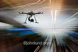 Drone surveillance is the primary concept behind this stock photo of a camera-equipped drone against a high tech background of streaking light trails.
