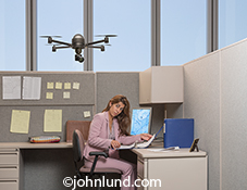 Drone pictures. A drone hovers over a woman office worker and points a camera lens at her in a stock photo about surveillance, privacy issues, corporate espionage, and future technology.