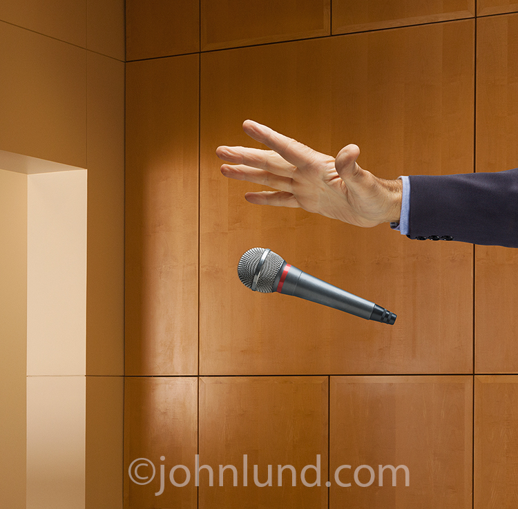A businessman's had drops the mic in a corporate lobby in this drop the mic stock photo about definitive and final business moves, sealing the deal, and business success.