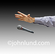 Drop the mic, or dropping the microphone, is illustrated simply and effectively in this stock photo of a man's hand, against a gradated grey background, dropping a  mic.
