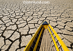 A bright yellow boat is left high and dry on a vast plain of cracked dry earth in a stock photo about drought, scarcity and water issues.
