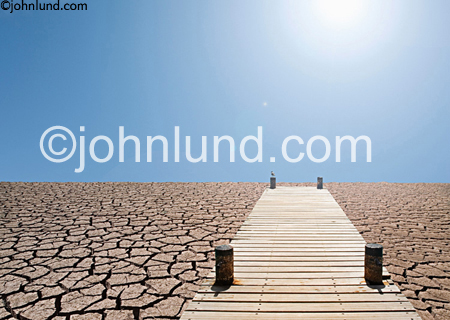 A pier stretches out over a landscape of dried earth in a photograph that speaks of drought and ecological and environmental disaster. Dry cracked land picture. Hot bright sun is visible.