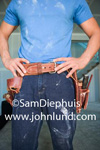 Carpenter or drywall contractor standing with hands on hips, dirty, and wearing a tool belt. Blue t shirt and jeans.  Torso only photo for advertising remodeling services and construction.