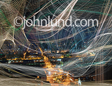 This dynamic and colorful image portrays a city connected through networks and wireless communications, surrounded and eveloped in webs of streaming data.