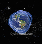 A swirling blue energy field envelopes the planet earth in this stock photo about energy, global communications, and science.