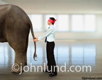 A businessman wears a blindfold while feeling the tail of an elephant to illustrate a narrow vision and point of view,