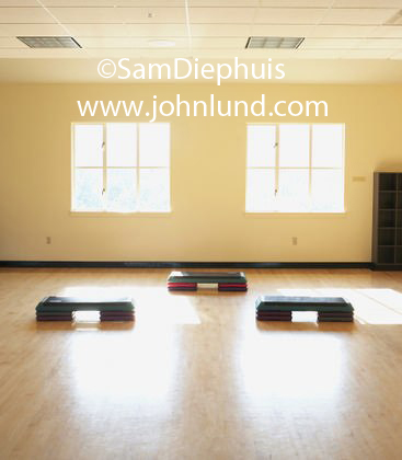 An empty yoga or dance studio after classes are over and everyone has left the building.  Plenty of light coming in through two large windows on the back wall. Yoga mats are on the hardwood floor.