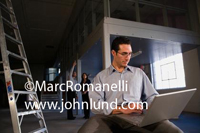 Picture of a man in an office under construction sitting with a laptop computer open on his lap.  An aluminum ladder is next to him.  Several people in the background. New Office pic.