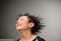 A young mixed-race happy boy shakes his head to fling the water out of his hair in an exhuberant stock photo.