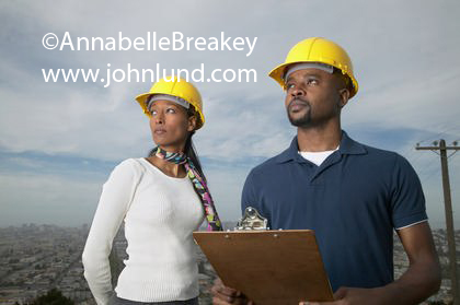 Picture of ethnic construction workers. A black man and a black woman are standing high above a city in the background on the side of a hill. They are looking off into the distance.  Construction worker pics for ads.