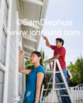 Couple painting their house. They are using paint brushes to paint the trim on their home. They are making home improvements. Picture of people painting a house.