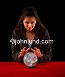 A businesswoman or psychic medium sees money in a crystal ball. With her hands hovering over the crystal ball images of Euro bank notes or money are visible floating in the ball.