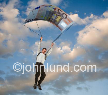 Businessman parachuting down from the sky using a Euro Note as a parachute. It's a picture of a golden parachute.  Executive abuse of power photo.