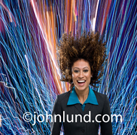 Vivid color streaks of light show energy and motion in this photo of an excited woman executive with her hair flying up.