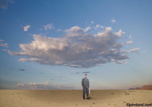 A business man stands alone on a desolate plain with a large cloud hanging over his head in this concept stock photo.
