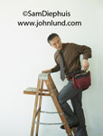 PIcture of an Asian or Chinese man dressed in a suit and wearing a tool belt as he climbs a ladder.  Man on a wooden step ladder with a workmans tool belt. Businessman with toolbelt pics.
