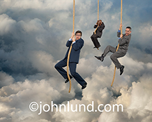 Three executives hand at the end of their ropes in a cloud bank in this stock photo about the challenges for businesses in cloud computing.