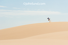 An active senior jumps up and clicks his heels together on top of a sand dune on the island of Socotra in Yemen in a metaphorical image for vitality, energy and travel.