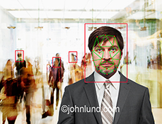Facial recognition in a crowd is the concept in this stock photo of a man's face with recognition software indications over it, against a backdrop of the rushiing figures of a crowd in a public space.
