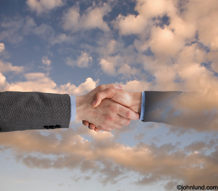 As two hands shake, one fades away into the sky symbolizing a tenuous deal, a questionable or uncertain outcome. Picture of shaking hands.