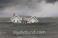 A family of three, mother, father and daughter, sit on the roof of their house as it floats in flood waters.